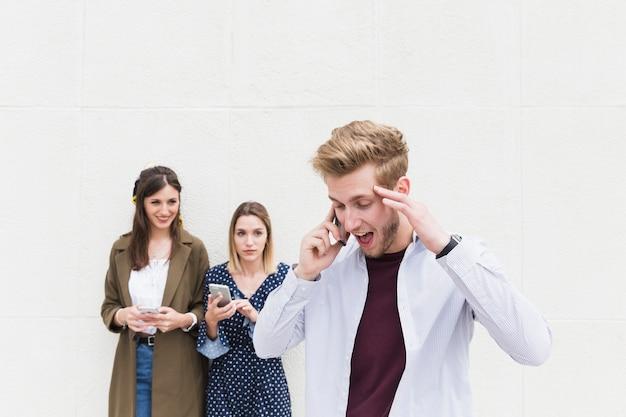 Twee vrouwen die de mens bekijken die op mobiele telefoon spreken