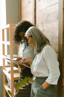 Twee vrouwen die een digitale tablet vasthouden en praten over enkele financiële aspecten