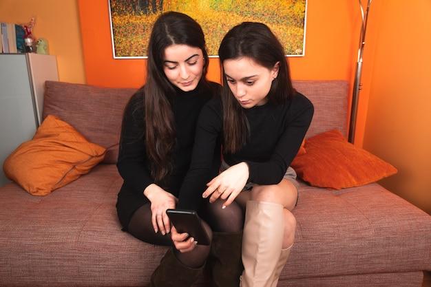 Twee vrouwen die een mobiele telefoon op de bank gebruiken