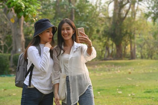 Twee vrouwen die een smartphone gebruiken en op de universiteit staan
