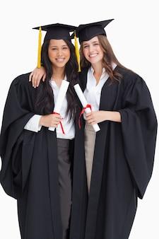 Twee vrouwen die elkaar omhelzen nadat ze afgestudeerd zijn aan de universiteit