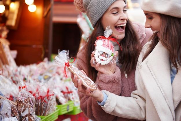 Twee vrouwen die gemberbrood op kerstmarkt kopen