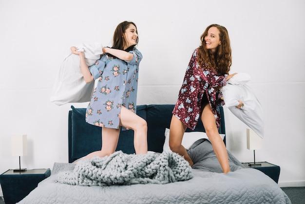 Twee vrouwen die grappige hoofdkussenstrijd op bed hebben