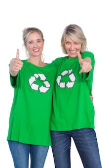 Twee vrouwen die groene recyclingst-shirts dragen die duimen opgeven