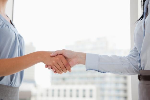 Twee vrouwen die handen op het kantoor schudden