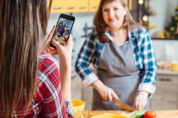 Twee vrouwen die het kookproces op smartphone filmen