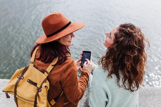 Twee vrouwen die het uitzicht van porto bij de rivier bekijken en een foto maken met een mobiele telefoon. reis- en vriendschapsconcept