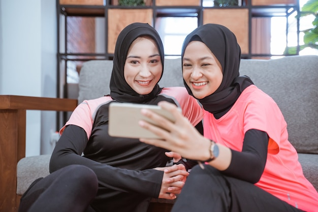 Twee vrouwen die hijab-sportkleding dragen die glimlachen terwijl ze selfies nemen samen met een mobiele telefoon terwijl ze op de grond in het huis zitten