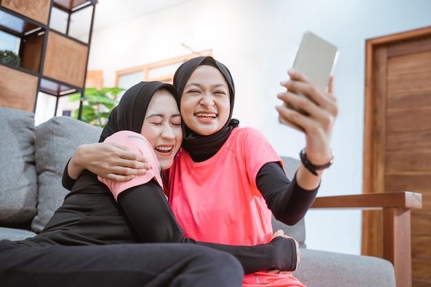 Twee vrouwen die hijab-sportkleding dragen, lachen en knuffelen tijdens een videogesprek met een mobiele telefoon terwijl ze op de grond in het huis zitten