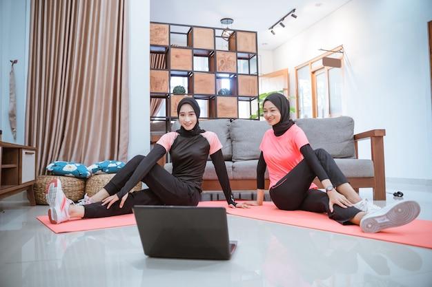 Twee vrouwen die hijab-sportkleding dragen, zitten op de grond terwijl ze hun heupen samen in huis opwarmen