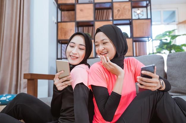 Twee vrouwen die hijabsportkleding dragen, lachen als ze op de grond in huis naar het scherm van een mobieltje kijken
