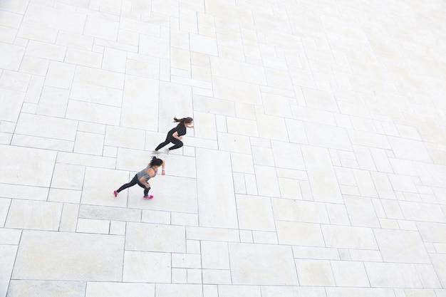 Twee vrouwen die in de stad, luchtmening lopen