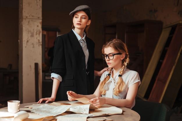 Twee vrouwen die in retro kleding brief lezen