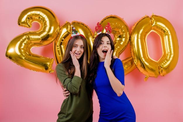 Twee vrouwen die kerstmishoepel dragen en voor gouden 2020 die ballons koesteren over roze worden geïsoleerd