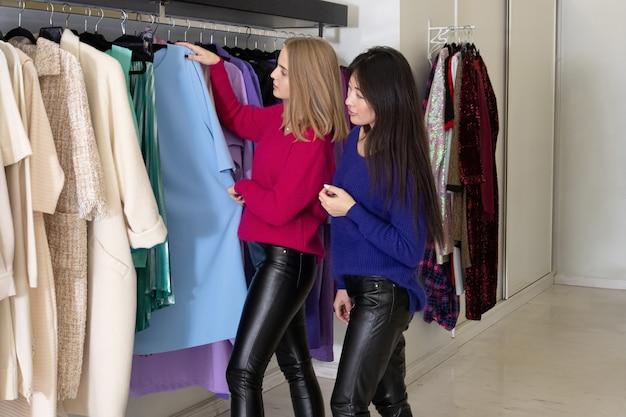 Twee vrouwen die kleren kiezen op winkelhangers