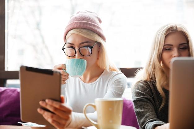 Twee vrouwen die koffie drinken en tablet in koffie gebruiken