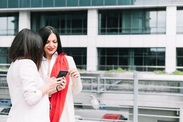 Twee vrouwen die mobiele telefoon bekijken