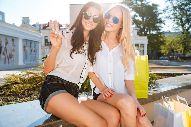 Twee vrouwen die na het winkelen samen op een bank rusten en overwinningsgebaar tonen