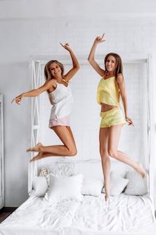 Twee vrouwen die pret hebben die op het bed springt