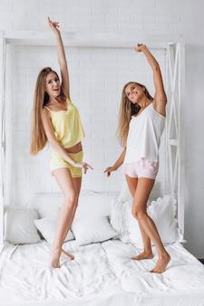 Twee vrouwen die pret op het bed hebben