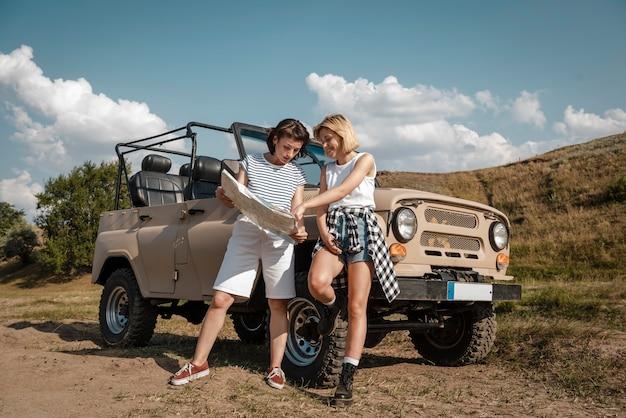 Twee vrouwen die samen de kaart controleren terwijl ze met de auto reizen