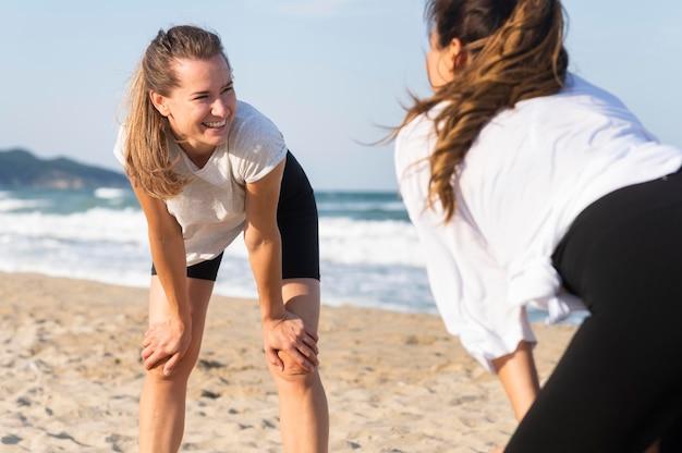 Twee vrouwen die samen op het strand oefenen