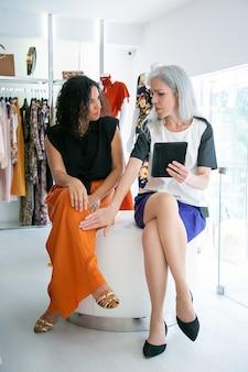 Twee vrouwen die samen zitten en tablet gebruiken, kleren en aankopen in modewinkel bespreken. vooraanzicht. consumentisme of winkelconcept