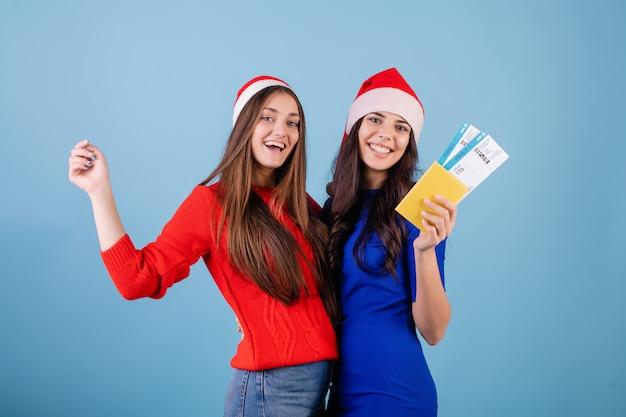 Twee vrouwen die santahoeden met vliegtuigkaartjes en paspoort dragen dat over blauw wordt geïsoleerd