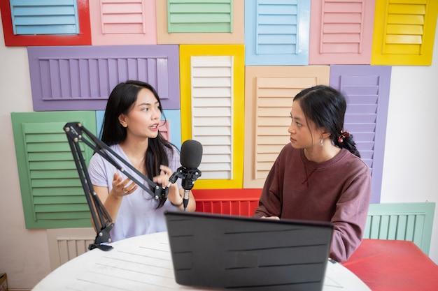 Twee vrouwen die serieus praten en microfoons gebruiken tijdens het opnemen van podcast