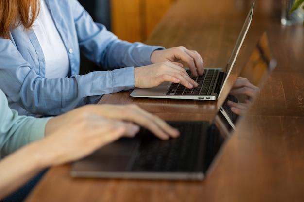 Twee vrouwen die tekst typen op een laptop europese zakenvrouwen die e-mails verzenden vanaf een computer