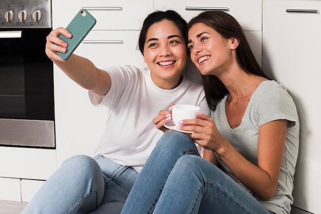 Twee vrouwen die thuis in de keuken een selfie maken
