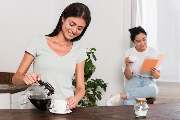 Twee vrouwen die thuis koffie hebben en lezen