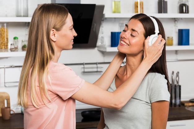 Twee vrouwen die thuis naar muziek op hoofdtelefoons luisteren