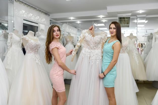Twee vrouwen die trouwjurk kiezen in de winkel