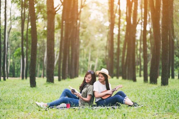 Twee vrouwen die ukelele spelen en samen een boek lezen in het bos