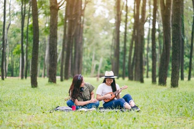Twee vrouwen die ukelele spelen terwijl ze samen in het bos zitten