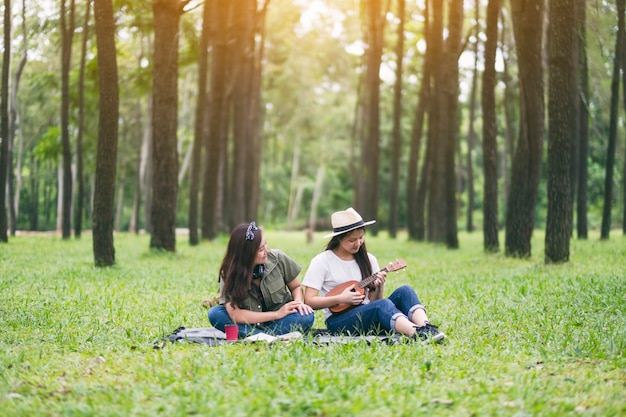Twee vrouwen die ukelele spelen terwijl ze samen zitten en ontspannen in het bos