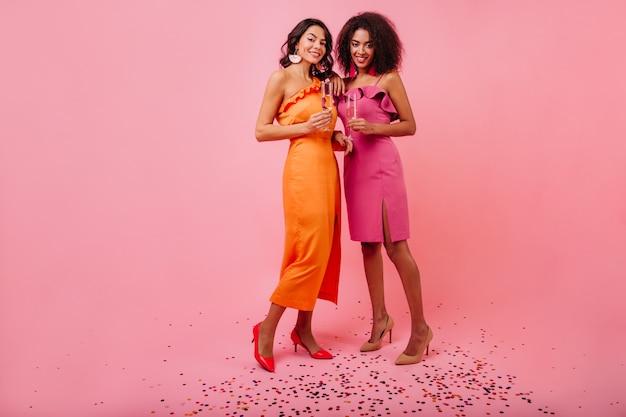Twee vrouwen die zich op fonkelingsconfettien bevinden