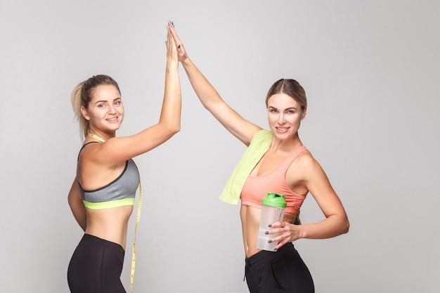 Twee vrouwen die zich verheugen, maken een zware training af. studio opname