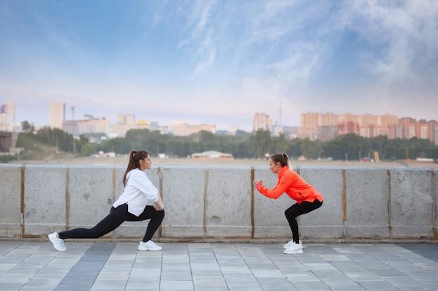 Twee vrouwen doen yoga-oefeningen in opleiding op een stadsstraat in de zomer.