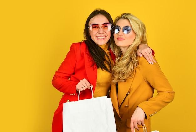 Twee vrouwen dragen boodschappentassen. grote verkoop en zwarte vrijdag. felle herfstkleuren. herfst en lente mode-stijl. trendy look voor elk seizoen. vriendschap en zusterschap. paar vrouwen gaan winkelen.