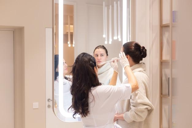 Twee vrouwen, een schoonheidsspecialiste-arts en een cliënt, staan tijdens een consult voor de spiegel en bespreken de komende procedures. schoonheidsspecialiste vertelt over het beeldhouwen van het gezicht