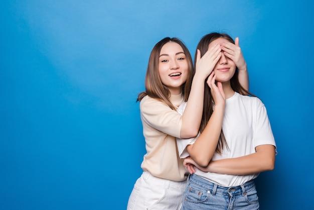 Twee vrouwen een verbergen ogen kijken niet raden wie casual t-shirts geïsoleerde blauwe muur dragen