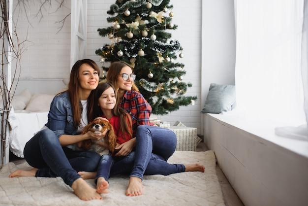 Twee vrouwen en een klein meisje met hond knuffelen in de buurt van de kerstboom