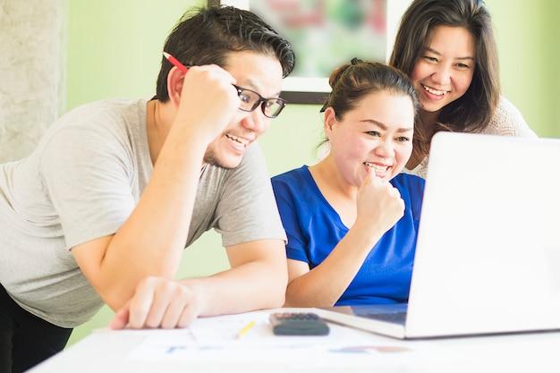 Twee vrouwen en één man kijken gelukkig computer in modern bureau