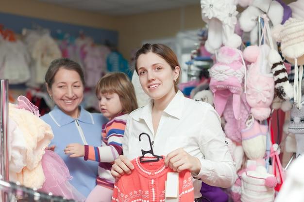 Twee vrouwen en kind bij klerenopslag
