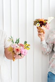 Twee vrouwen houden bloemen in ijshoorntjes omhoog