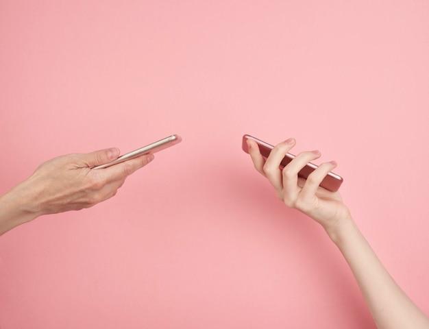 Twee vrouwen houden telefoon op pastelroze