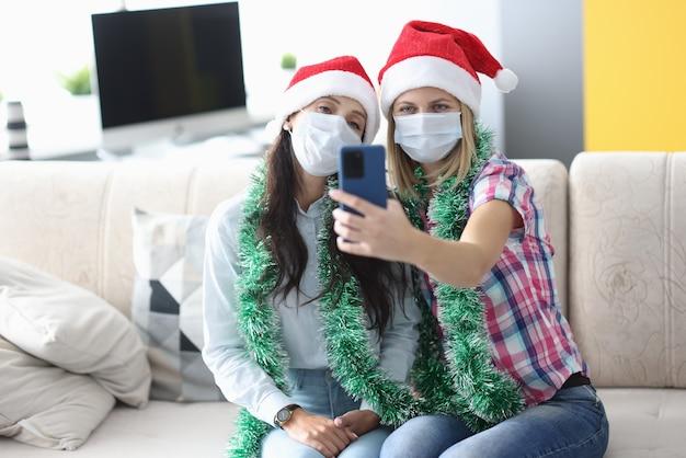 Twee vrouwen in beschermend masker nemen selfie op telefoon.