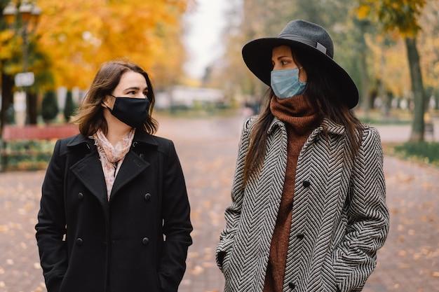 Twee vrouwen in beschermende maskers lopen in het park